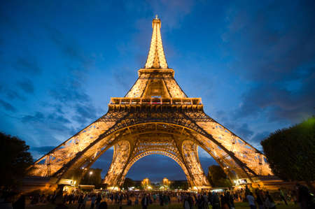 monument historical monument: PARIS, FRANCE - JULY 27, 2015: Tourists are visiting the eiffel tower in the twilight in Paris in France