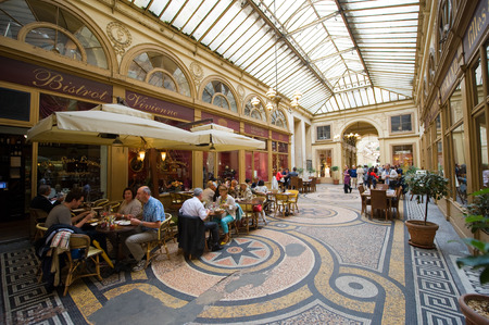 PARIS, FRANCE - JULY 27, 2015: Galerie Vivienne is an ancient historical passage with shops and restaurants and a tourist attraction in Paris in France