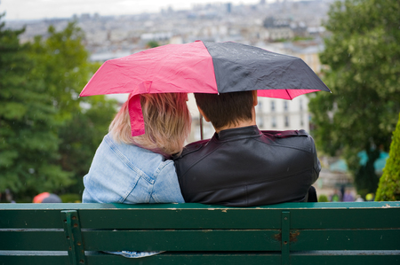 couple in rain: PARIS, FRANCE - JULY 27, 2015: A couple is sitting on a bench under an umbrella during a rainy day in Mont Matre in Paris in France