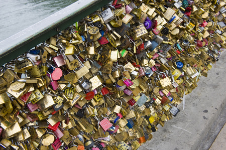 keylock: PARIS, FRANCE - JULY 28, 2015: Thousands of padlocks on a fence near the Pont des Arts symbolize love forever in Paris in France