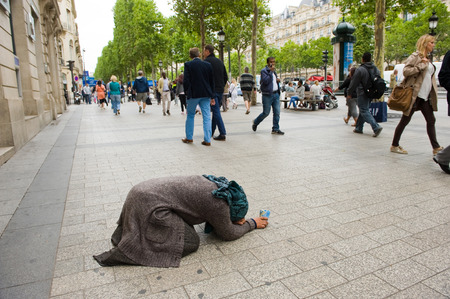 disgrace: PARIS, FRANCE - JULY 28, 2015: A homeless woman is begging for money on the Champs-Elysees in Paris in France