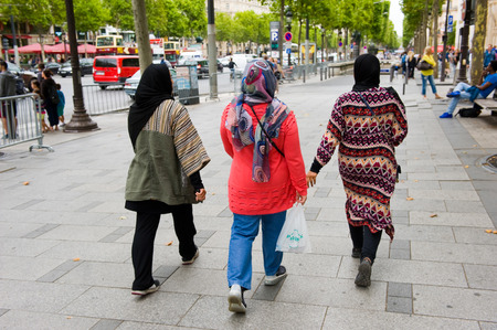 head scarf: PARIS, FRANCE - JULY 28, 2015: Three muslim woman with head scarf are walking on the Champs-Elysees in Paris in France