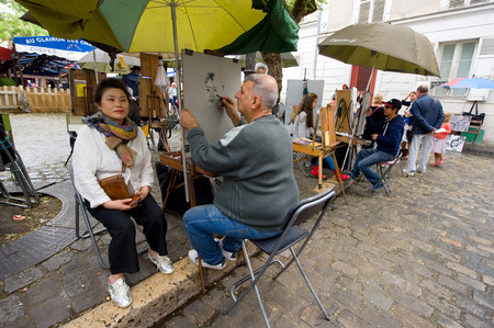 parisian: PARIS, FRANCE - JULY 27, 2015: A painter is painting a portrait of a tourist on Place du Tertre in Montmartre, one of the most famous tourist attractions in Paris in France