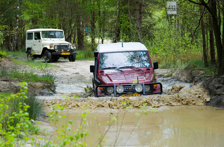 4wd: FURSTENAU, GERMANY - MAY 09, 2015: A Toyota is driving through a pond of water on a special off the road terrain for land cruisers and vehicles in Germany