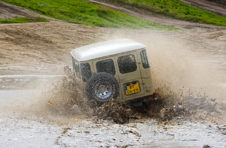 terrain: FURSTENAU, GERMANY - MAY 09, 2015: A Toyota 4-wheel drive is driving through a pond of water on a special off the road terrain for land cruisers and vehicles in Germany