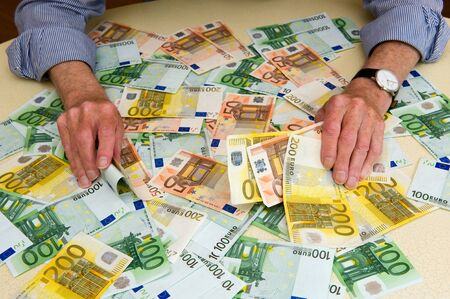 banknotes: An elderly man with a lot of euro banknotes on the table Stock Photo