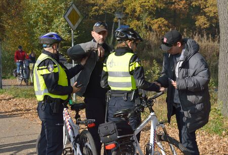 patrol officer: ENSCHEDE, THE NETHERLANDS - OCT 31, 2015: Police women are checking people for ID and weapons before a demonstration against migrant refugees camps for syrians Editorial