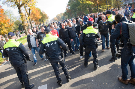 migrant: ENSCHEDE, THE NETHERLANDS - OCT 31, 2015: People are demonstrating against a huge migrant refugee camp for syrians close to the part of the city where they live. Police man are stopping them.