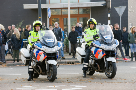motorcycle officer: ENSCHEDE, THE NETHERLANDS - OCT 31, 2015: Two policemen on motorcycles on the street are watching the traffic. Editorial