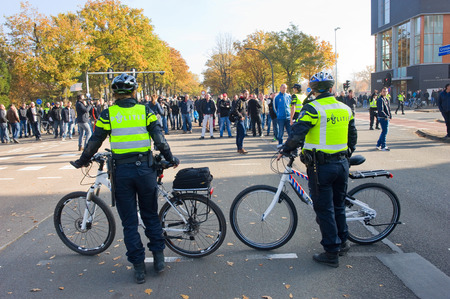 they are watching: ENSCHEDE, THE NETHERLANDS - OCT 31, 2015: People are demonstrating against a huge migrant refugee camp for syrians close to the part of the city where they live. Police are watching them.