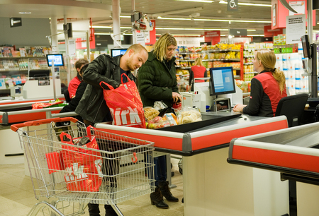 ENSCHEDE, THE NETHERLANDS - OCT 15, 2015: A couple is paying het products they just  bought in the Dirk supermarket at the cashier. Editorial