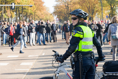 police woman: ENSCHEDE, THE NETHERLANDS - OCT 31, 2015: People are demonstrating against a huge migrant refugee camp for syrians close to the part of the city where they live. A police woman is watching them. Editorial
