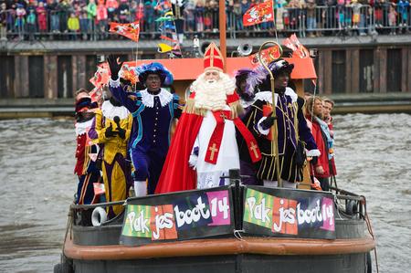 ENSCHEDE, NEDERLAND - 14 november 2015: De Nederlandse Kerstman genaamd 'Sinterklaas' is aankomen met zijn hulp Zwarte Piet op een stoomboot in een haven in Nederland. Stockfoto - 54917567