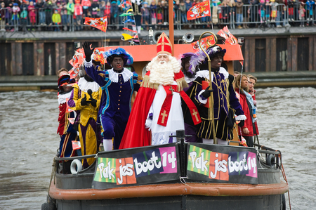 ENSCHEDE, NEDERLAND - 14 november 2015: De Nederlandse Kerstman genaamd 'Sinterklaas' is aankomen met zijn hulp Zwarte Piet op een stoomboot in een haven in Nederland.