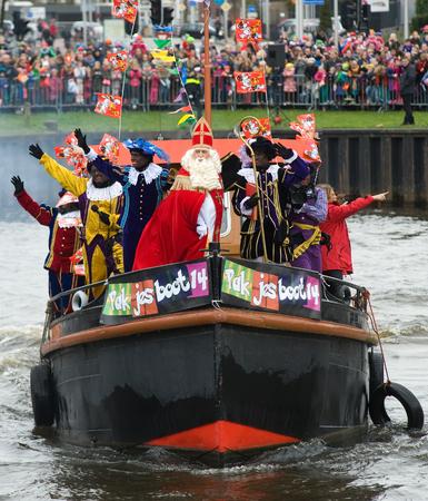 ENSCHEDE, NEDERLAND - 14 november 2015: De Nederlandse Kerstman genaamd 'Sinterklaas' is aankomen met zijn hulp Zwarte Piet op een stoomboot in een haven in Nederland. Stockfoto - 54917569