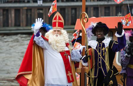 ENSCHEDE, NEDERLAND - 14 november 2015: De Nederlandse Kerstman genaamd 'Sinterklaas' is aankomen met zijn hulp Zwarte Piet op een stoomboot in een haven in Nederland. Stockfoto - 54917577