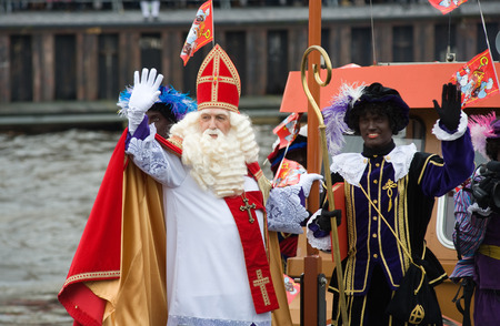 nicolas: ENSCHEDE, THE NETHERLANDS - NOV 14, 2015: The dutch Santa Claus called Sinterklaas is arriving with his help Black Pete on a steamboat in a harbor in Holland.