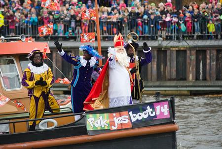 ENSCHEDE, NEDERLAND - 14 november 2015: De Nederlandse Kerstman genaamd 'Sinterklaas' is aankomen met zijn hulp Zwarte Piet op een stoomboot in een haven in Nederland. Stockfoto - 54917578