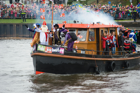 nicolaas: ENSCHEDE, THE NETHERLANDS - NOV 14, 2015: The dutch Santa Claus called Santa Claus is arriving with his help Black Pete on a steamboat in a harbor in Holland.