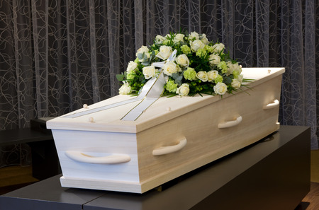 pass away: A coffin with a flower arrangement in a morgue