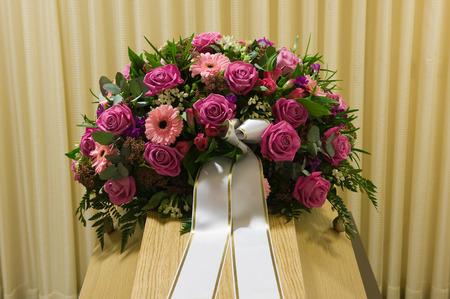 morgue: A coffin with a flower arrangement in a morgue