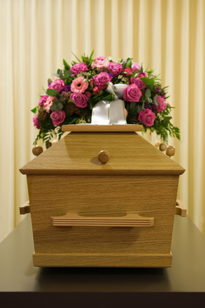undertaker: A coffin with a flower arrangement in a morgue