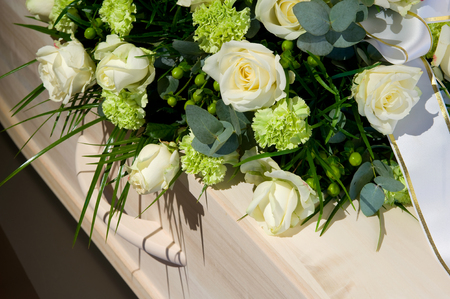 Een kist met een bloemstuk in een lijkenhuis