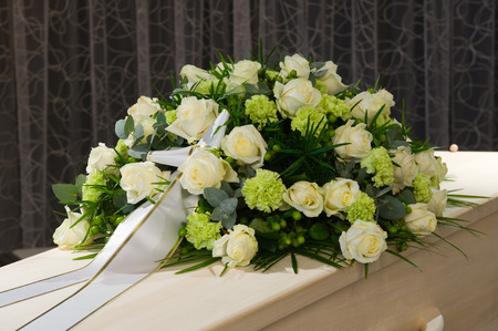 funeral: A coffin with a flower arrangement in a morgue