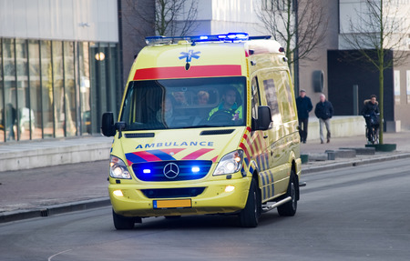 ambulance: ENSCHEDE, NETHERLANDS - JAN 22, 2016: An ambulance is rushing with speed to the hospital