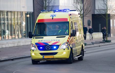 ambulancia: ENSCHEDE, PAÍSES BAJOS - 22 DE JULIO DE 2016: Una ambulancia corre a toda velocidad al hospital