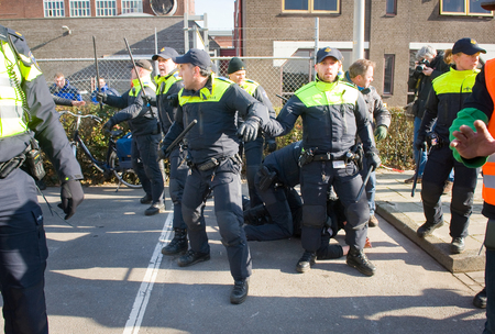 being arrested: ENSCHEDE, THE NETHERLANDS - FEB 13, 2016: A demonstrator against a huge migrant refugee camp for refugees is being arrested by policemen. Editorial