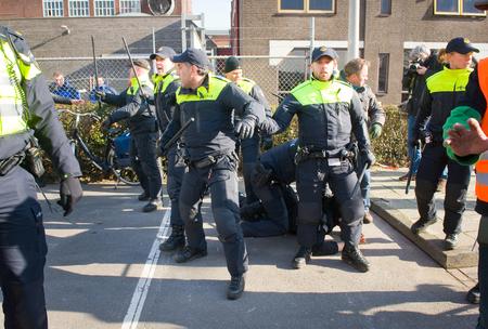 demonstrator: ENSCHEDE, THE NETHERLANDS - FEB 13, 2016: A demonstrator against a huge migrant refugee camp for refugees is being arrested by policemen. Editorial