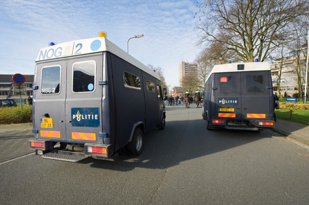 they are watching: ENSCHEDE, THE NETHERLANDS - FEB 13, 2016: People are demonstrating against a huge migrant refugee camp for syrians close to the part of the city where they live. Police are watching them.