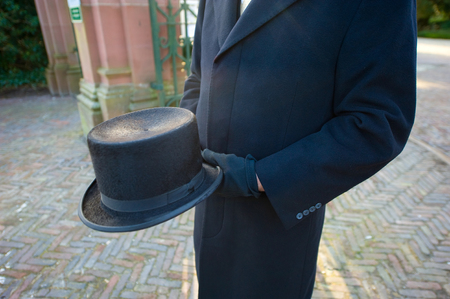 cremation: A funeral leader with a hat in his hands is waiting on a cemetery