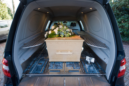 grave: A coffin in a mourning car with a flower arrangement