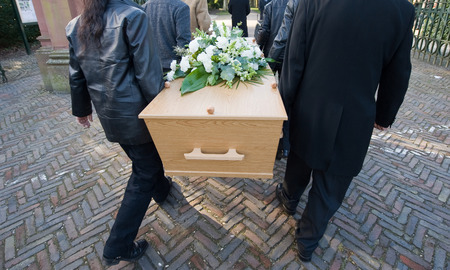 undertaker: Six peoply are carrying a coffin on to a cemetery