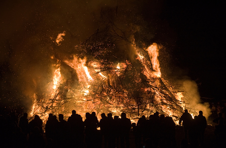 People are watching a huge bonfire, a tradition with easter in Nort-West Europe.