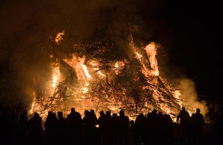 Mensen kijken naar een groot vreugdevuur, een traditie met Pasen in Nort-West-Europa.