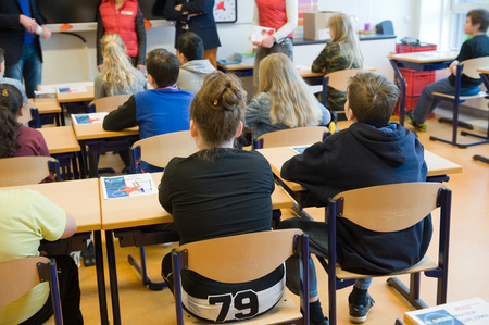 11 years: ENSCHEDE, NETHERLANDS - MAR 22, 2016: Kids of 11 years old sitting behind their desks in a school class.