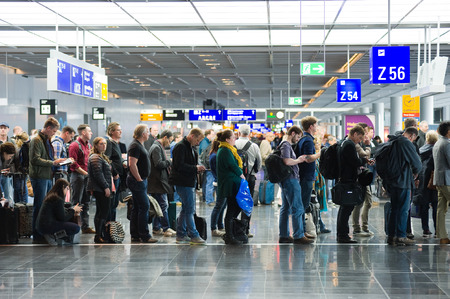FRANCFORT, Alemania - 25 de abril, 2016: Los pasajeros esperando en una fila para el embarque en un aeropuerto para un vuelo a América Foto de archivo - 56983487