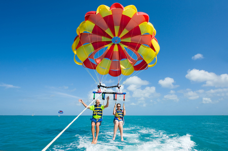 parasailing: KEY WEST, FLORIDA, USA - MAY 02, 2016: An elderly couple is para sailing with a rope pulled by a boat near Key West in Florida