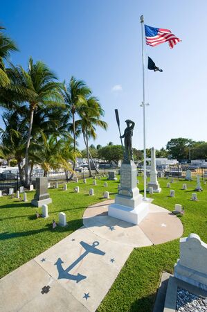 gravesite: KEY WEST, FLORIDA, USA - MAY 02, 2016: Statue and American flag at the middle of the battleship Maine memorial section at the Key West cemetery.