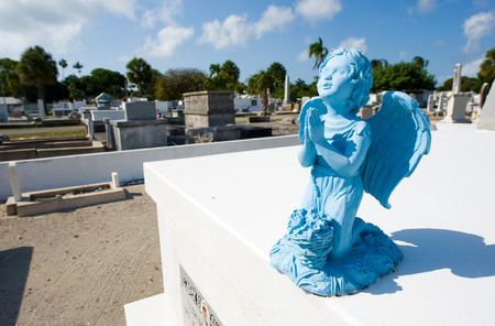 angel headstone: KEY WEST, FLORIDA, USA - MAY 02, 2016: Blue angel on the grave at Key West cemetery.  It is a 19-acres cemetery, and about 100.000 people are buried here.