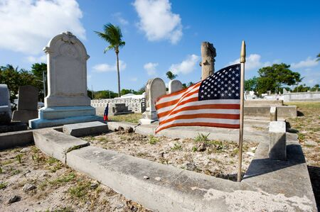 KEY WEST, FLORIDA, USA - MAY 02, 2016: American flag on a grave at the The Key West cemetery. It is a 19-acres cemetery, and about 100.000 people are buried here.