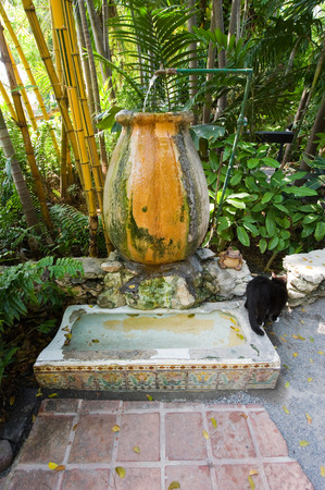 KEY WEST, FLORIDA, USA - MAY 03, 2016: Former urinal in the garden of the Ernest Hemingway House in Key West in Florida. It is now used by cats to drink.
