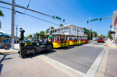 key west: KEY WEST, FLORIDA, USA - MAY 02, 2016: Tourists on the famous conch tour train riding and sightseeing through Duval street in the center of Key West