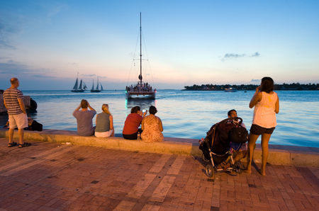 KEY WEST, FLORIDA, USA - MAY 03, 2016: Tourists are relaxing at the waterside in the twilight on Mallory Square in Key West in Florida.