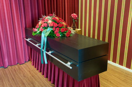undertaker: A coffin with flower arrangement in a morgue Stock Photo