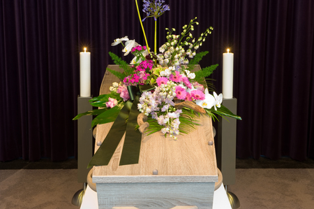 grieve: A coffin with flower arrangement in a morgue Stock Photo