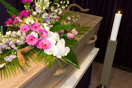 A coffin with flower arrangement in a morgue Stock Photo